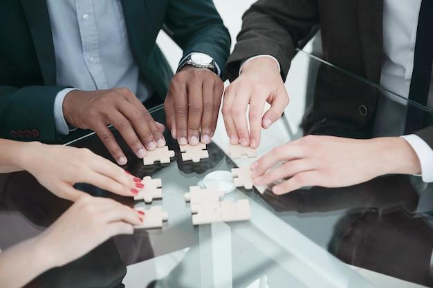 Closeup equipe de negócios multinacionais montando quebra-cabeça. o conceito de estratégia nos negócios