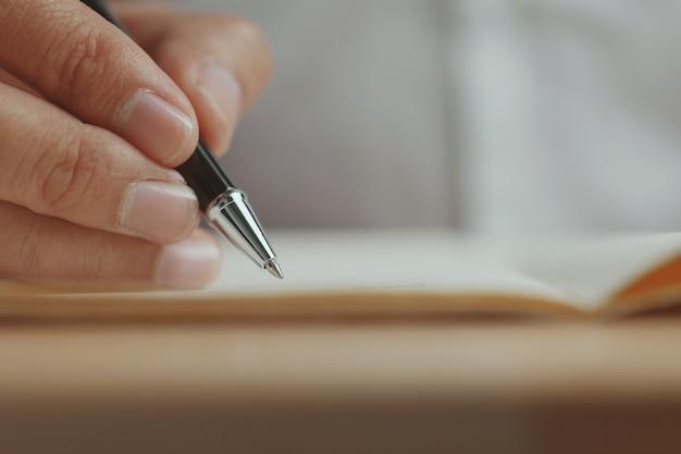 Closeup escrevendo em um pedaço de papel escrevendo cartas de amor com uma caneta