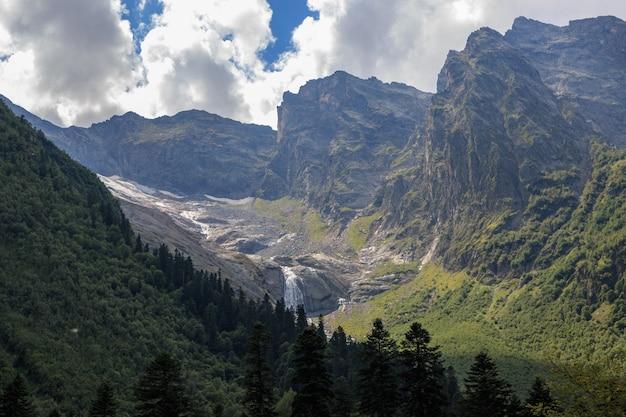 Closeup exibição de cenas de montanhas e cachoeira distante no parque nacional dombai, cáucaso, rússia, europa. paisagem de verão, clima ensolarado e dia ensolarado