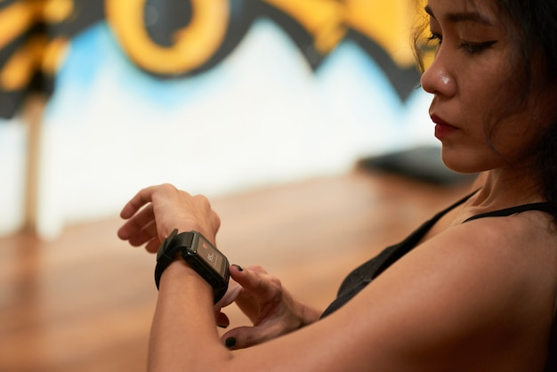 Closeup extrema de desportista asiática, verificação de pulso com dispositivo eletrônico