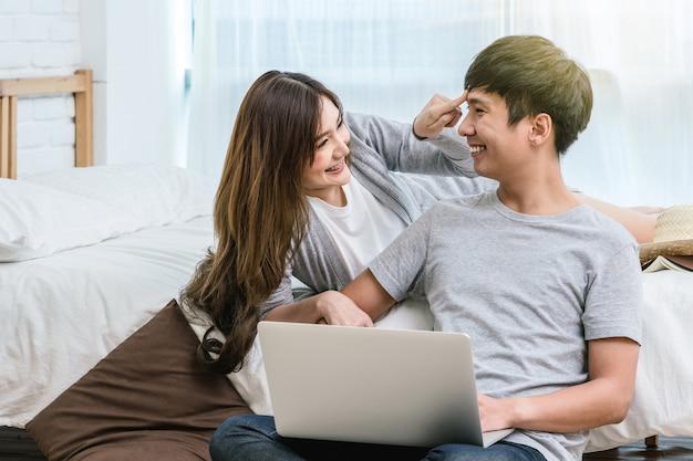 Closeup feliz amante asiática ou casal conversando e sorrindo ao usar o laptop na cama