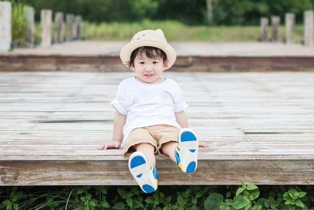 Closeup feliz garoto asiático com rosto sorriso sente-se no caminho de madeira no fundo do parque