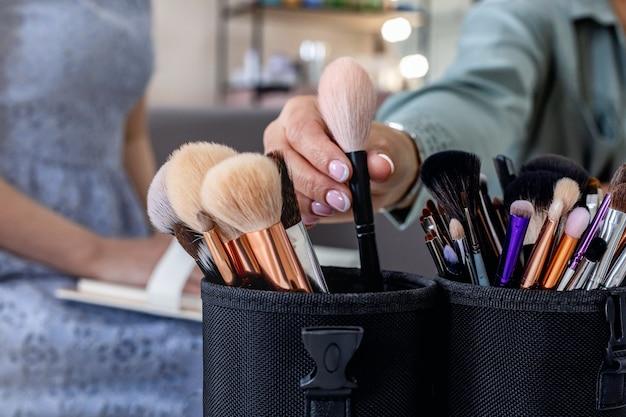 Closeup feminino maquiador com as mãos pegando um pincel para aplicar cosméticos, explicando ao cliente