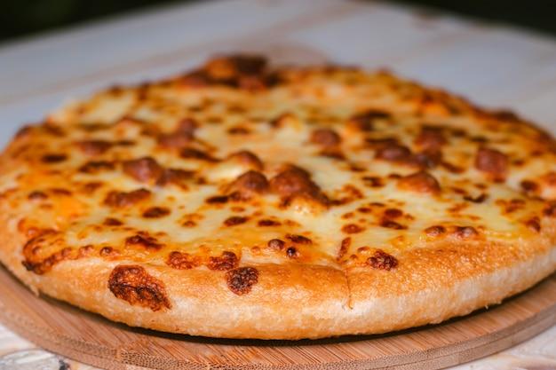 Closeup foco seletivo da pizza pronta para comer em uma bandeja de madeira sobre uma mesa de madeira.
