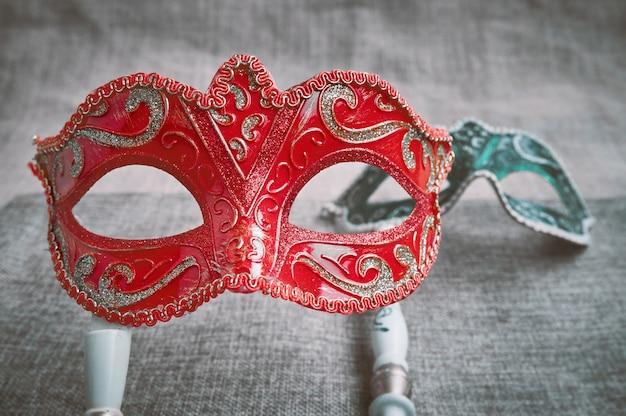 Closeup, foco seletivo no baile de máscaras veneziano vermelho, máscara de carnaval com máscara verde embaçada