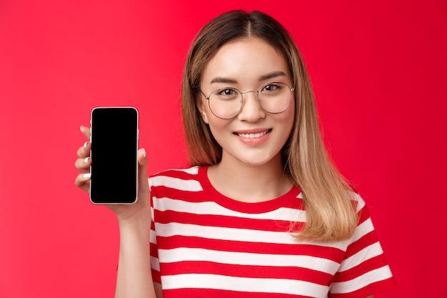 Closeup fofa loira asiática promove app de smartphone feminino blogueira mostrando pa ...