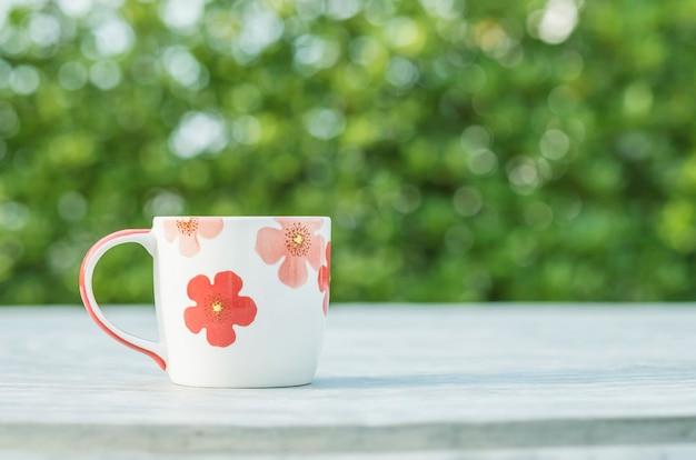 Closeup fofa xícara de café na mesa de concreto turva e vista para o jardim no plano de fundo texturizado de manhã