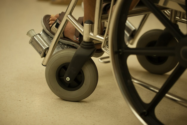 Closeup foot of patient man on wheelchair in hospital