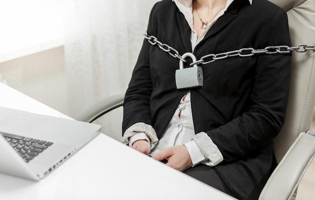 Closeup foto de empresária amarrada a uma cadeira por uma corrente de metal