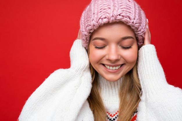 Closeup foto de linda adorável jovem loira em pé isolado sobre a parede de fundo colorido, vestindo roupas da moda todos os dias, mostrando emoções faciais.