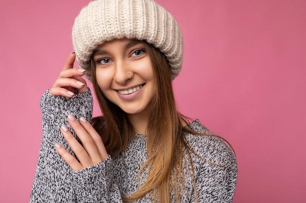 Closeup foto de linda feliz sorridente jovem loira escura em pé isolado sobre a parede de fundo colorido, vestindo roupas da moda todos os dias, olhando para a câmera, mostrando as emoções faciais.