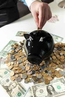 Closeup foto de mão colocando moeda no cofrinho preto