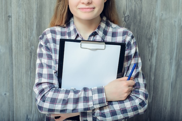 Closeup foto de mulher isolada em um fundo cinza de madeira segurando uma caneta e uma prancheta com papel em branco