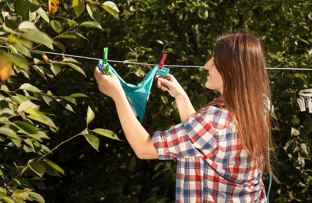 Closeup foto de mulher pendurada em um biquíni azul no varal no jardim