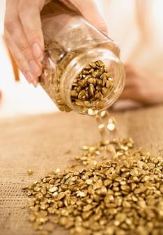 Closeup foto de mulher segurando barras de ouro cheias de pepitas de ouro