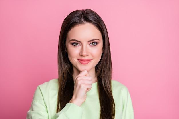 Closeup foto de senhora atraente engraçada com penteado comprido reto mão dedo no queixo pessoa criativa inteligente, amigável, sorridente, usar casual moletom verde pulôver isolado fundo de cor rosa