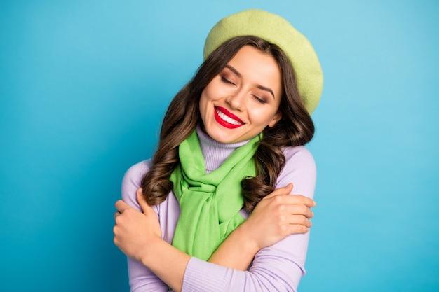 Closeup foto de uma encantadora senhora de olhos fechados, abraçando a si mesma paz conceito harmonia interna usar chapéu boina verde, lenço de moletom roxo isolado parede de cor azul