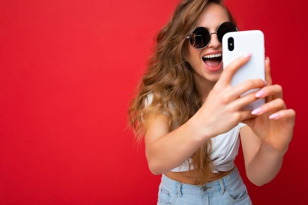 Closeup foto de uma linda jovem loira feliz incrível segurando um celular, tirando uma foto de selfie