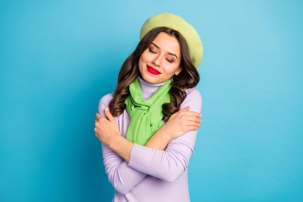 Closeup foto de uma linda senhora lábios vermelhos, olhos fechados, abraçando a si mesma paz conceito harmonia interna usar chapéu boina verde, lenço de gola alta roxo isolado na parede de cor azul