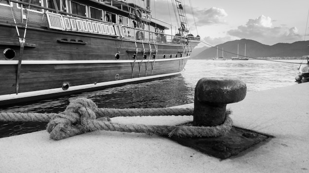 Closeup foto em preto e branco de um velho navio de madeira atracado e amarrado com corda grossa no porto marítimo