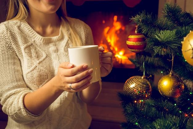 Closeup foto tonificada de mulher com suéter de lã se aquecendo na lareira com uma xícara de chá