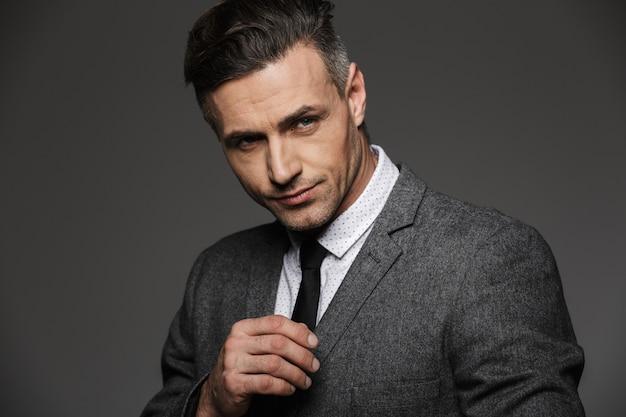 Closeup fotografia de homem profissional, vestindo terno formal com expressões faciais graves, isolado sobre parede cinza