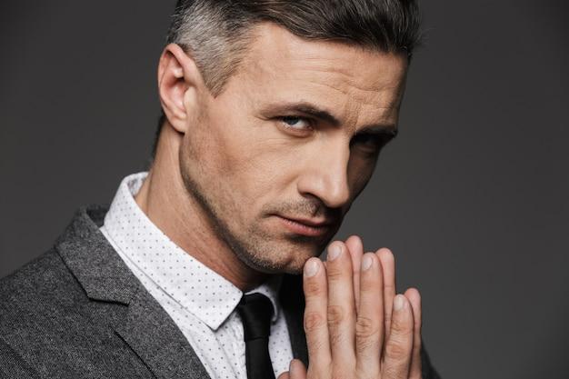 Closeup fotografia de homem sério elegante vestindo camisa branca e gravata, mantendo as palmas das mãos juntas em rezar pose, isolado sobre a parede cinza