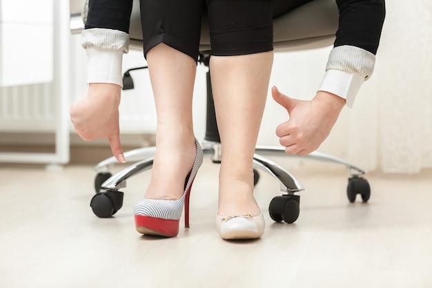 Closeup fotografia de mulher com sapato de salto alto e sapatilha com os polegares para baixo e para cima