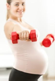 Closeup fotografia de mulher grávida feliz a posar com halteres
