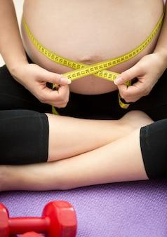 Closeup fotografia de mulher grávida sentada no tapete de fitness e medindo a barriga com fita adesiva