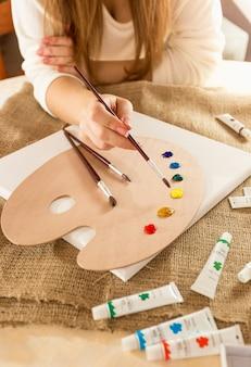 Closeup fotografia de uma jovem artista sentada à mesa a desenhar na tela