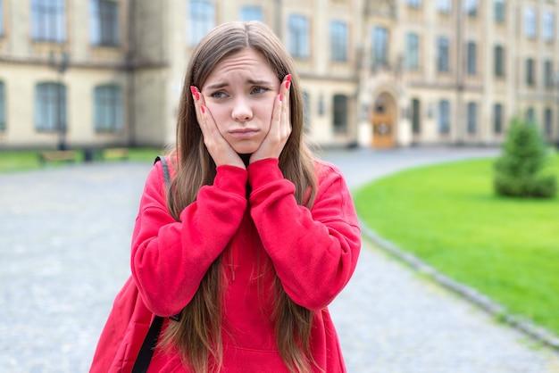 Closeup fotografia de uma menina adolescente pensativa e pensativa com uma expressão facial engraçada a tocar no rosto a pensar em má marca