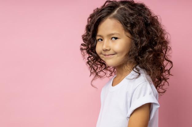 Closeup fotografia de uma menina engraçada de cabelos cacheados com olhar astuto, sorrindo com expressão astuta, vestindo camiseta branca, olhando com o espaço vazio.