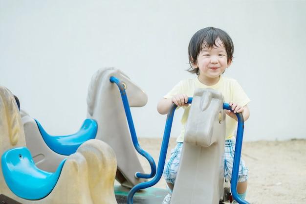 Closeup garoto feliz com cara de sorriso jogar brinquedo carrossel no parque infantil