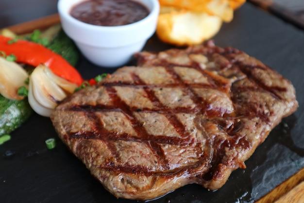 Closeup grelhado steak ribeye com molho de vinho tinto, servido na chapa de pedra quente