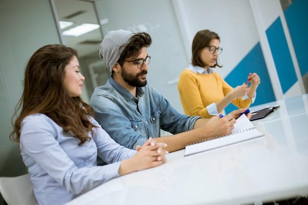 Closeup grupo jovens colegas de trabalho juntos discutindo o projeto criativo durante o processo de trabalho