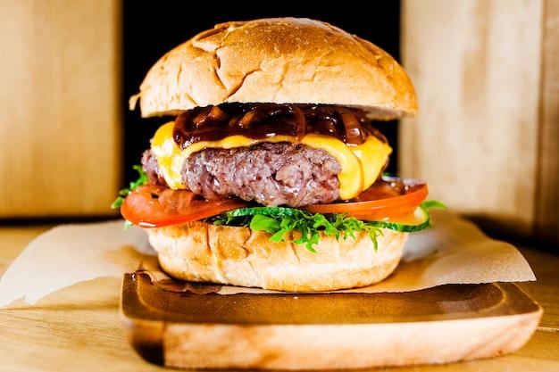 Closeup hambúrguer com costeleta de carne, legumes, queijo e molho de mirtilo.