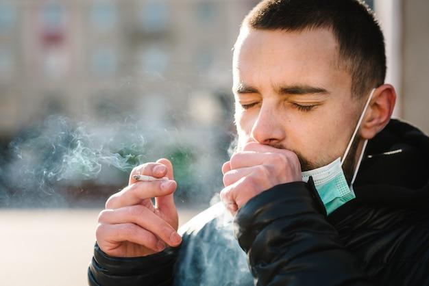 Closeup homem com máscara durante a pandemia de covid-19, tossindo e fumando um cigarro na rua.