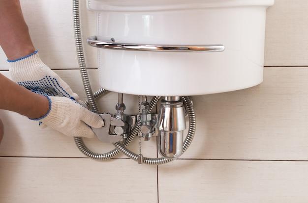 Closeup homem consertando a pia em um banheiro.