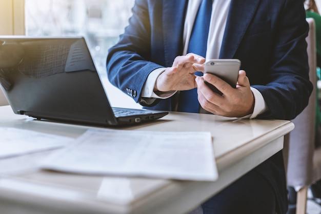 Closeup homem de terno, segurando em suas mãos um telefone celular e envia uma mensagem no celular interior