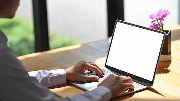 Closeup homem digitando o computador portátil de maquete na mesa de madeira.