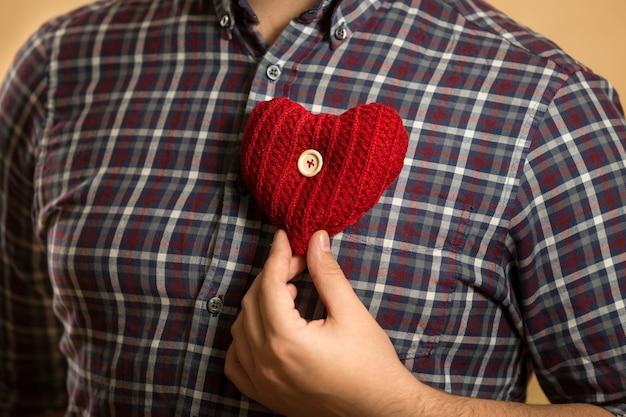 Closeup homem segurando um coração vermelho no peito