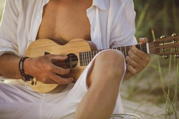 Closeup homem tocando cavaquinho durante as férias de verão na praia