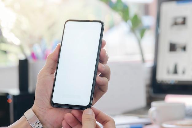 Closeup homem usando smartphone no escritório. tela em branco para montagem de exibição de gráficos.