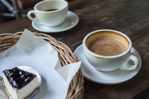 Closeup imagem de duas xícaras de café e um bolo na cesta na mesa de madeira vintage no café