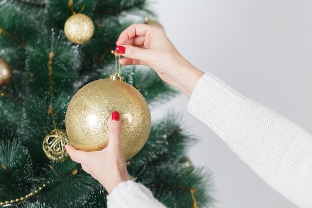Closeup imagem de mulher de camisola, decorar a árvore de natal com enfeites