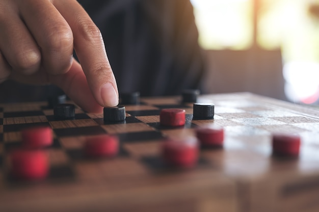 Closeup imagem de pessoas jogando e se movendo damas em um tabuleiro de xadrez