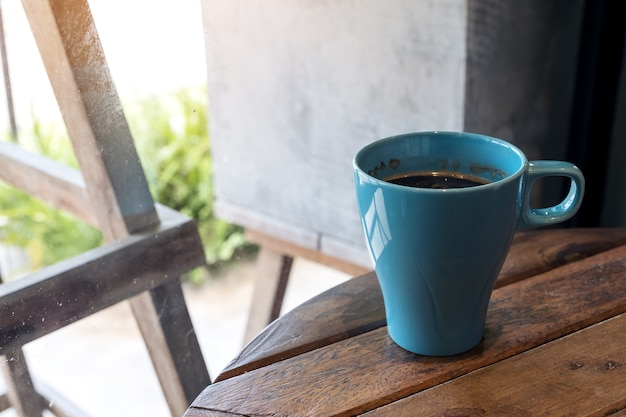 Closeup imagem de uma caneca azul de café quente na mesa de madeira vintage no café