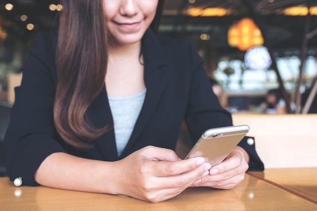 Closeup imagem de uma empresária asiática segurando, usando e olhando para smartphone
