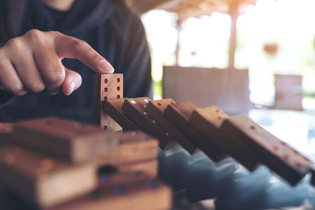 Closeup imagem de uma mão tentando impedir o jogo de dominó de madeira de cair na mesa